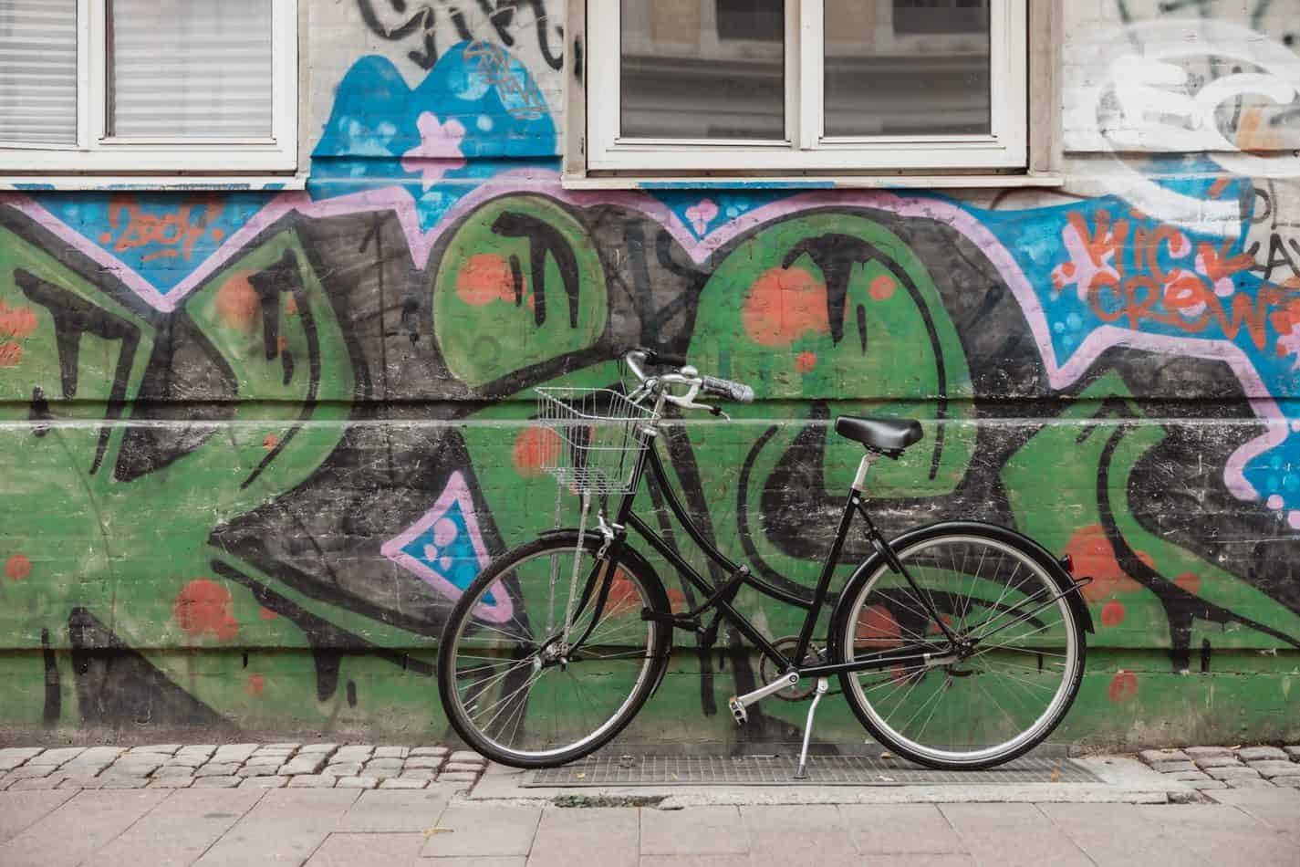 Black bicycle in front of green grafitti art
