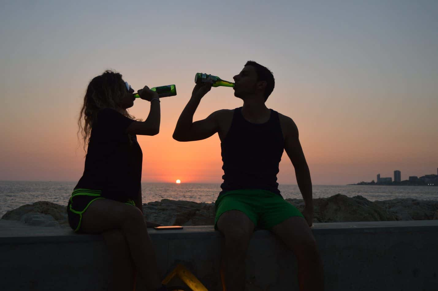 Two people drinking from bottles in the sunset.